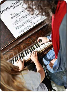 in home piano teacher giving advanced private piano lesson